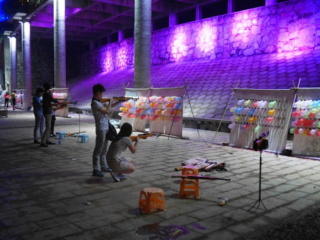 young woman and man shooting balloons at night in Hengyang, China