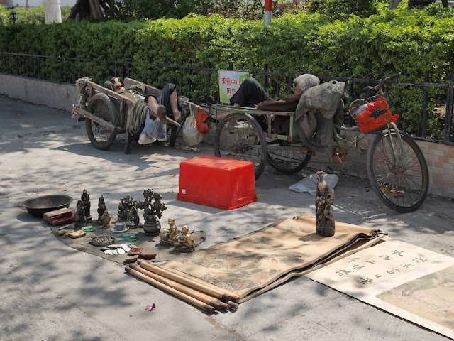 man sleeping in a wheelbarrow and a man sleeping in a tricycle cart next to antiques for sale