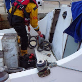 A crew member sets up a salvage pump aboard the catamaran - 24 December 2013.  Photo credit: RNLI/Poole