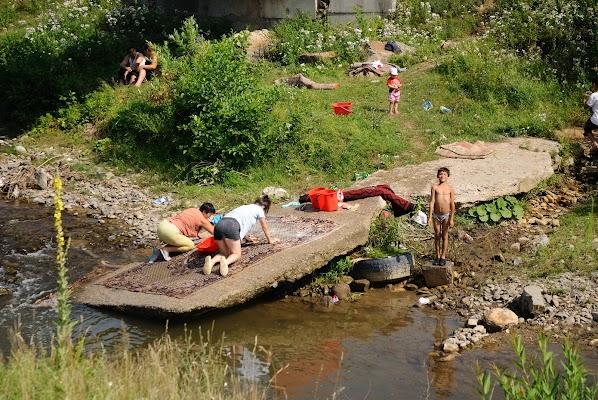 Frauen waschen einen Teppich im Fluss bei Zlatna