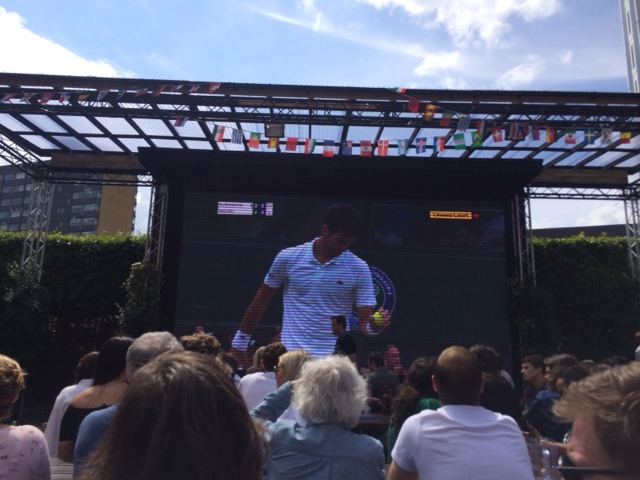 photo of tennis being shown on a big screen in a beer garden