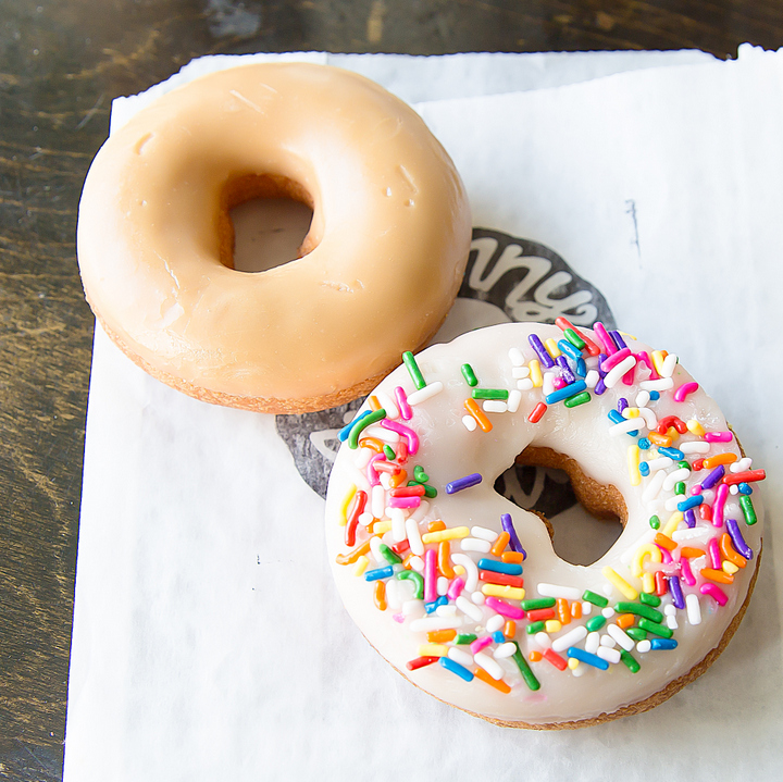 photo of a maple-glazed donut and sprinkle donut
