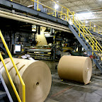 This begins the process of producing solid fiber slip sheets and tier sheets from rolls of paperboard.