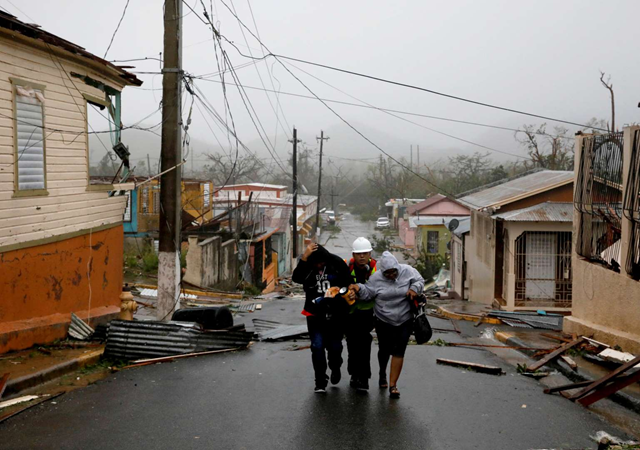 Rescue workers help people after the area was hit by Hurricane Maria in Guayama, Puerto Rico, on 20 September 2017. Photo: Carlos Garcia / Reuters