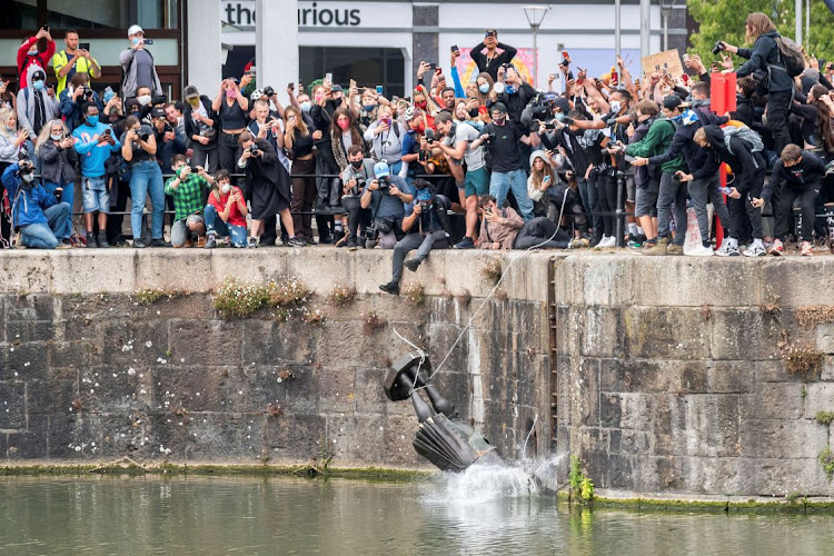 The statue of 17th-century slave trader Edward Colston falls into the water after protesters pulled it down and pushed into the docks during a protest against racial inequality in Bristol, Britain, June 7 2020. Picture: VIA REUTERS/KEIR GRAVIL