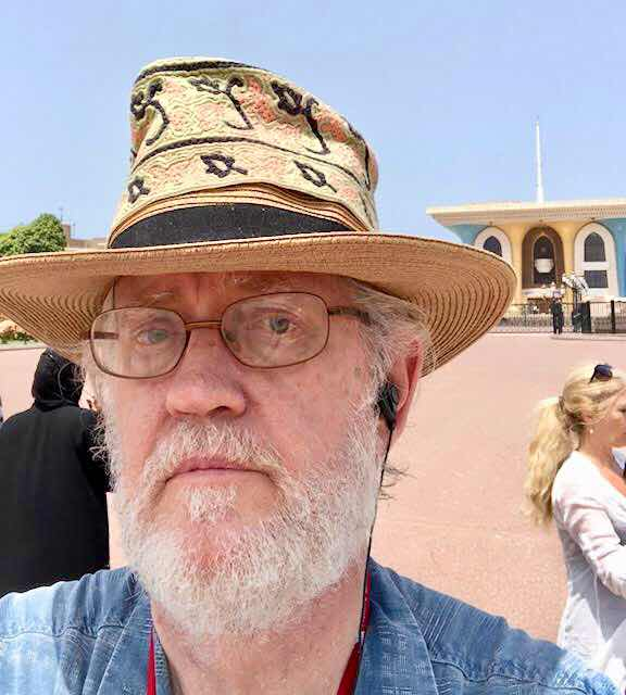Resident Astronomer George with Omani hat combo in front of Sultan of Oman palace