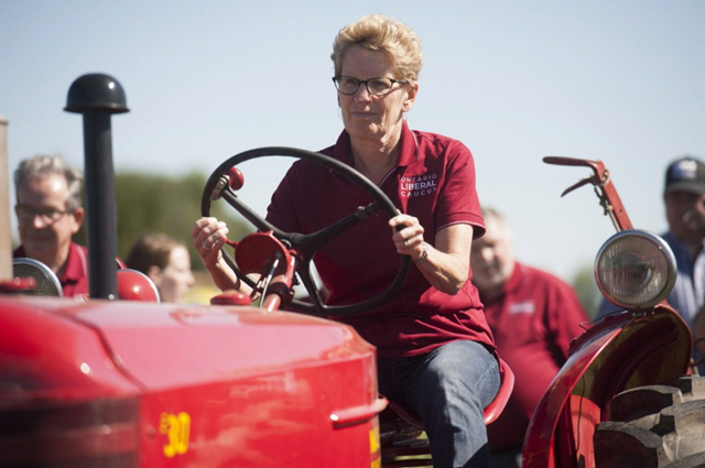 Premier Kathleen Wynne was shadowed by wind farm protesters in September 2016 at the International Plowing Match and booed over hydro prices. Photo: Hannah Yoon / THE CANADIAN PRESS
