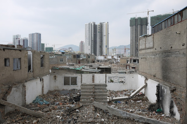 Demolished homes with new buildings in the background in Xining, Qinghai