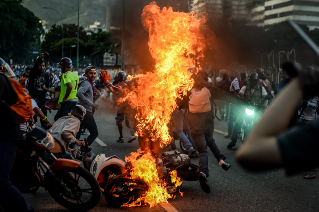 Vigilantism has occurred during protests in Venezuela. In this photo, demonstrators set fire to Orlando Figuera, a man accused of stealing at a protest. Photo: Meridith Kohut / The New York Times