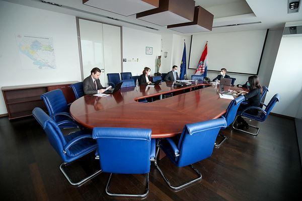 Les membres de la présidence croate sont assis dans la salle de téléconférence en maintenant la distanciation sociale.