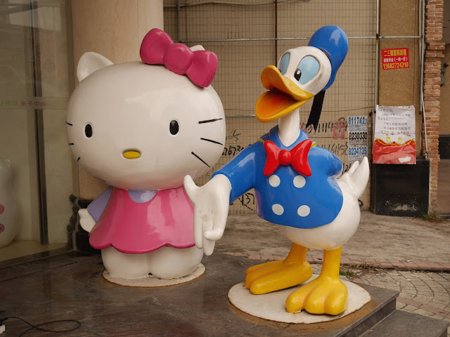 Sculpture of Donald Duck holding out his hand next to a sculpture of Hello Kitty