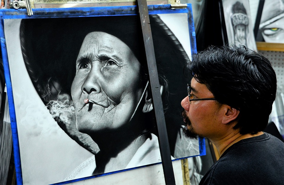 Artist in Chiang Mai with black and white picture of a local in a large hat, smoking