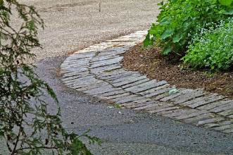 Photo: The homeowner was always driving over the garden edge. We cut limestone wall coursing into cobble stones and sloped it up from the drive to make the driveway larger and guide car tires away from the garden.