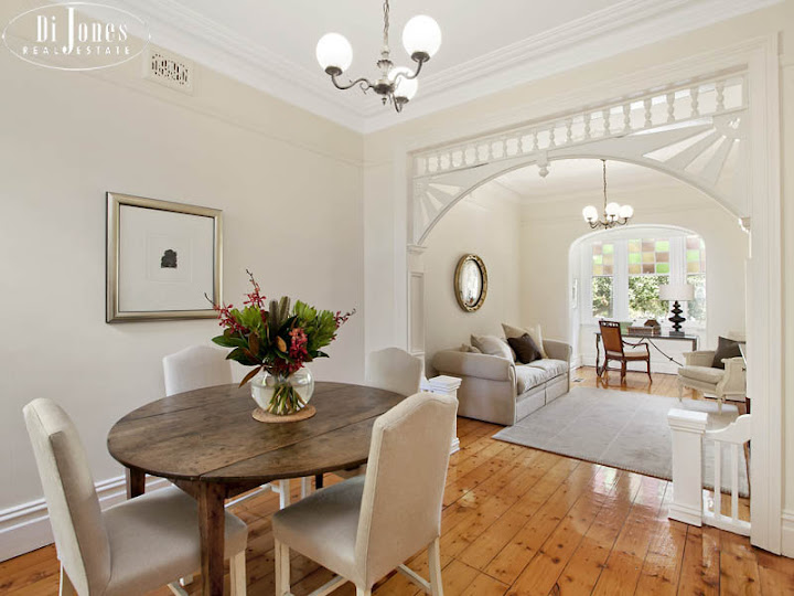 Ornamental timber arch separates the private dining room from the formal sitting room; A solitary chair graces the nook in the bay window to the right