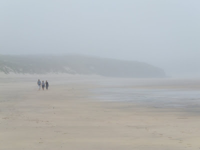 Three people trek along the fog bound sands