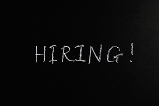 """A black chalkboard with writing that reads, """"HIRING!"""""""