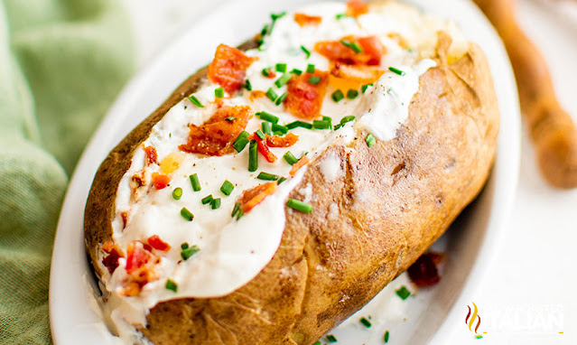 instant pot baked potatoes on a plate fully loaded