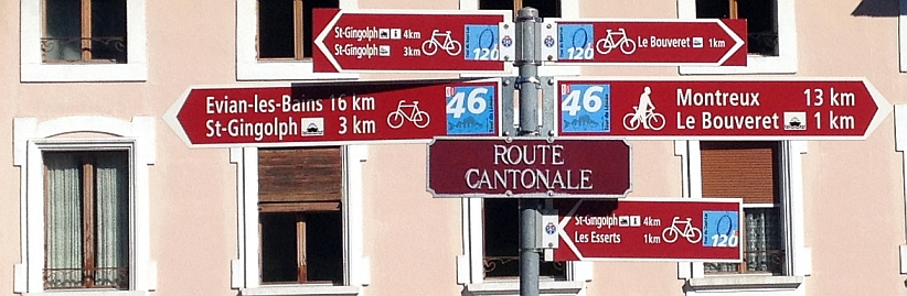 Schweizer Fahrrad-Radweg-Schilder auf der Route Cantonale vor dem Institut de l'Ecole des Missions (Impasse du Bout de la Foret 5,1898 St-Gingolph,Schweiz)