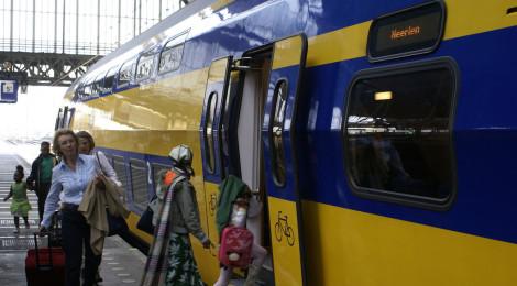 Reizigers stappen in de trein naar Maastricht op spoor 5a van het Centraal Station in Amsterdam.