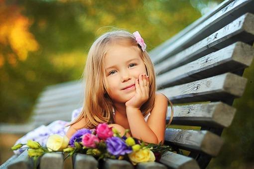 Девочка лежит на лавке с букетом цветов
