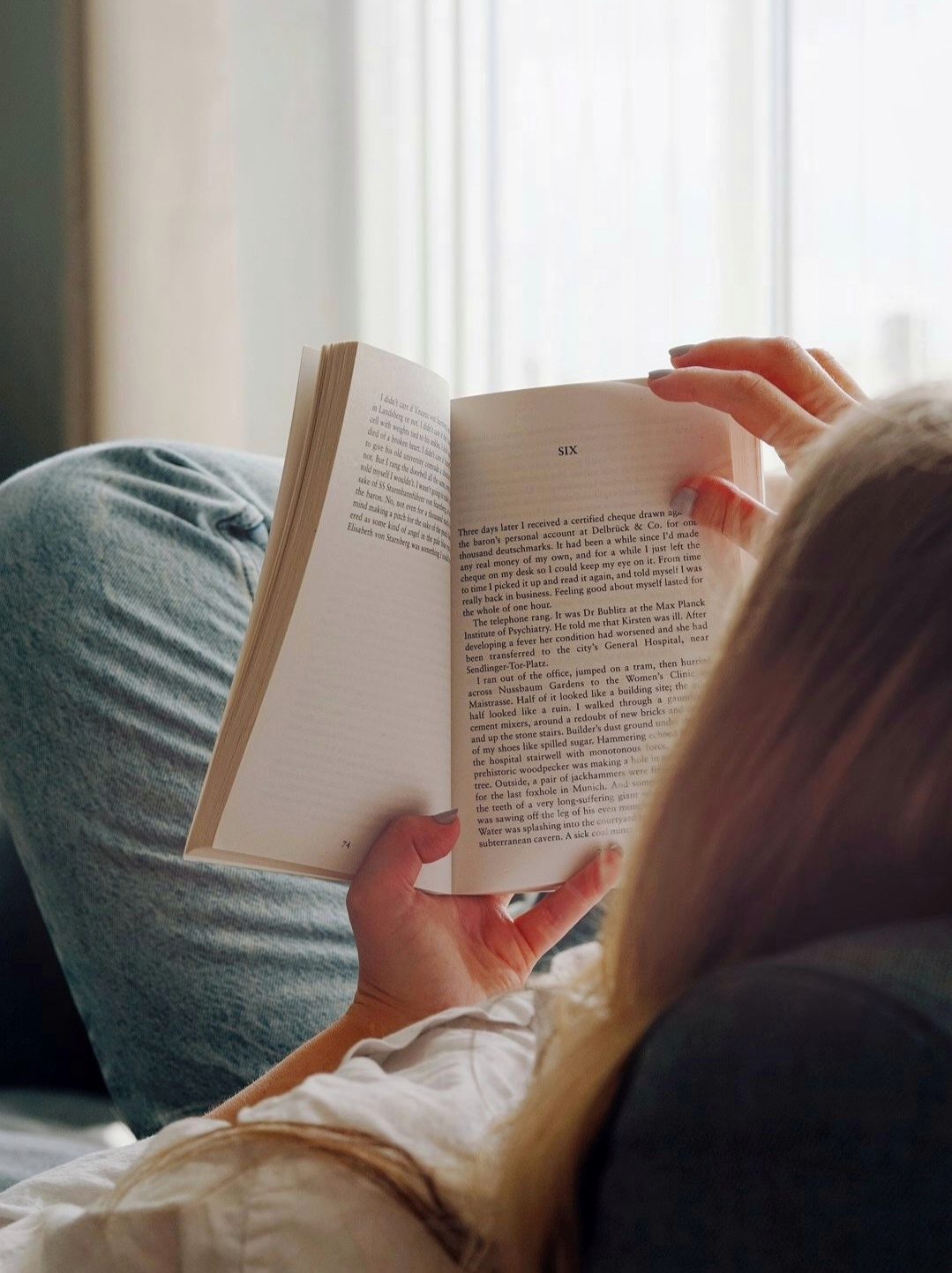 woman laid on sofa reading a book