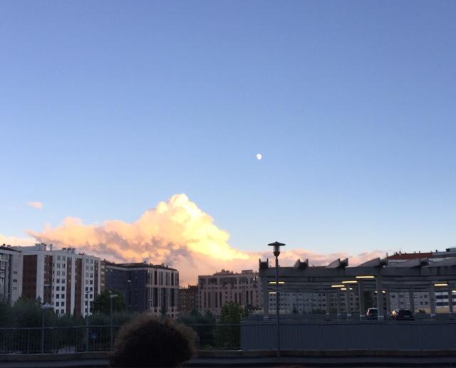 El sol poniente tiñe de naranja y rosa unas nubes que semejan una montaña en el horizonte.