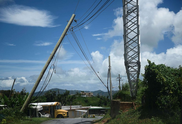An electric power pole leans over the road in the Piedra Blanca area of Yabucoa, Puerto Rico, 16 May 2018. Photo: Carlos Giusti / AP
