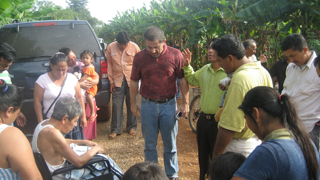 Fellow missionary Paul Kazim prays with the residents of Limon.