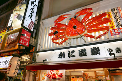 Sights of Osaka - Left, Kushikatsu Daruma a kushikatsu restaurant (deep fried skewer restaurant) whose mascot is an angry looking Asian chef with a fu manchu. And, to the right another location of crab restaurant Kani Doraku that erected their giant mechanized crab sign back in 1960 and kicked off a craze of giant animated seafood signs