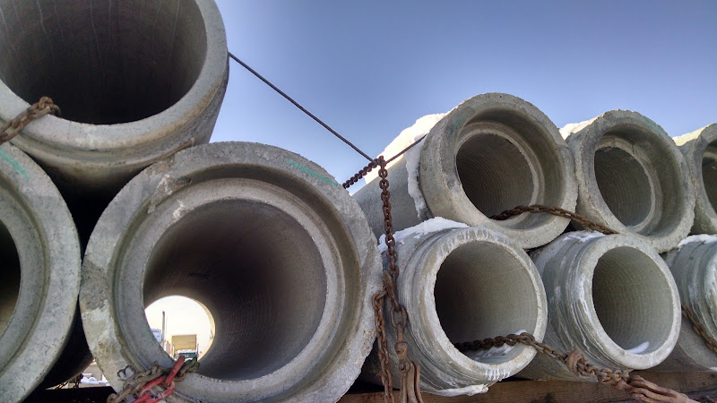 concrete pipes loaded and chained eyes crosswise on flatbed trailer in winter snow