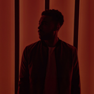 Man in profile standing against red background at night