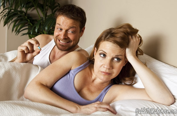 Man and woman in bed with Viagra pill