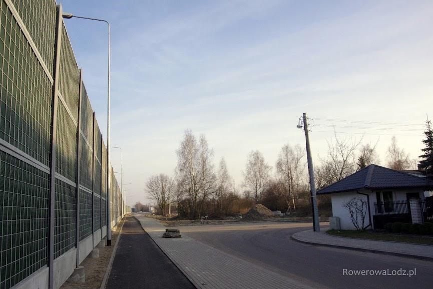 Latarnie wciśnięte w skrajnie drogi dla rowerów, ale oświetlające tylko to co po jednej stronie muru.