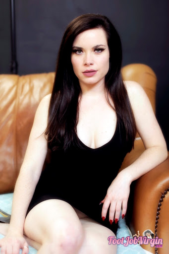 Jasmin Jai sitting on a couch in a black mini dress