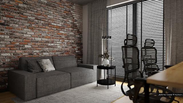 Gabinet do pracy w loftowym stylu. Szara kanapa na tle czerwonej cegły, tuż przed nią znajduje się czarny stolik na nóżkach.