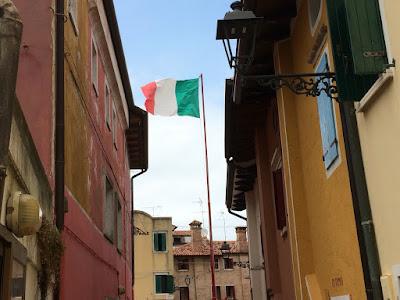 Et italiensk flagg som vaier i enden av en trang bygate.