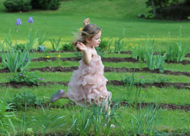 girl in pink dress running through a garden