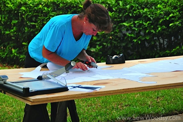 Woman using a box cutter to cut paper on wood.