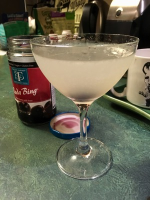 A frosty white cocktail with cherry at the bottom of the glass, a container of dark cherries behind