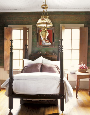 this wood colonial four poster bed looks at home in the room weathered green painted walls shutters an antique light fixture and bare hardwood floors