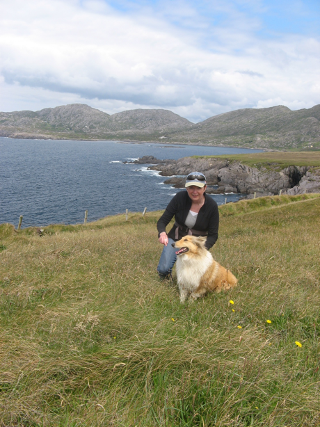 woman walking with a collie dog, field overlooking the ocean