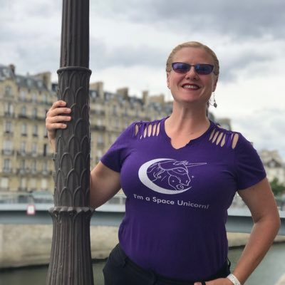 """Crystal M. Huff, standing next to a lamp post with a purple """"I'm a Space Unicorn"""" t-shirt"""