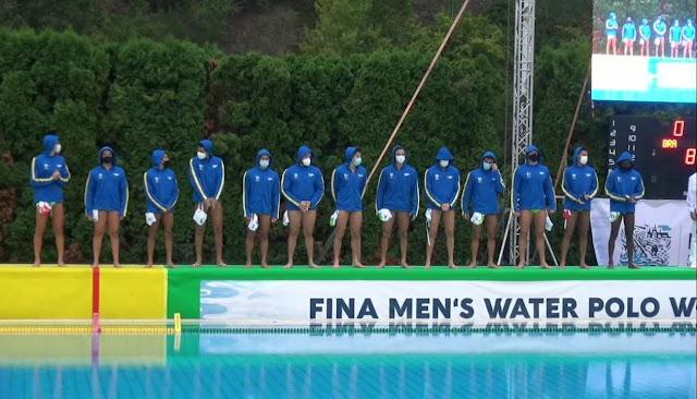 Seleção masculina sub-20 de polo aquático alinhada do lado de fora da piscina. Os altetas vestem sunga e um moletom azul com capuz