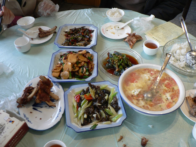 assorted dishes and a big glass bowl of rice at a restaurant in Wuhan, China
