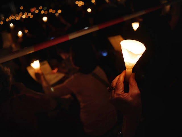 hand holding a candle at the vigil in Victoria Park, Hong Kong, commemorating the anniversary of the Tiananmen Square crackdown