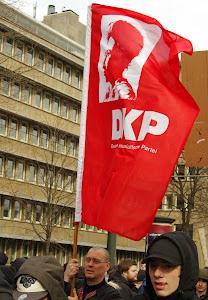Demonstranten mit DKP-Fahne.