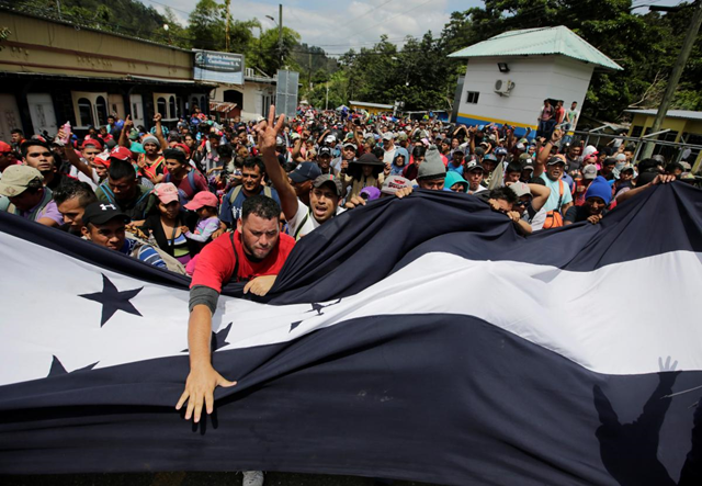 Honduran migrants, part of a caravan trying to reach the U.S., gesture while arriving to the border between Honduras and Guatemala, in Agua Caliente, Guatemala, 15 October 2018. Jorge Cabrera / REUTERS