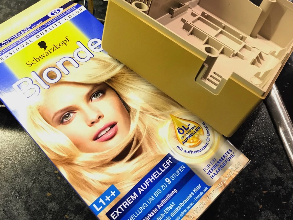 Schwarzkopf commercial hair bleaching product. Amiga Power Brick case part, yellowed, laying next to it.