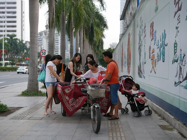 people buying fruit from a fruit vendor using a motorized tricycle cart