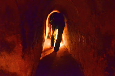 A tourist bends to walk through the tunnels